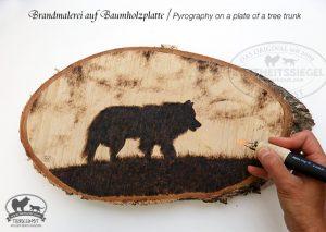 Brandmalerei auf einem Baumstamm